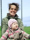 Bébé avec sa maman sur une oscillation image stock