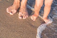 Bébé avec sa promenade de mère sur la plage Photo libre de droits