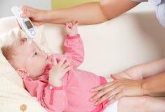 Bébé avec un thermomètre numérique Photo libre de droits