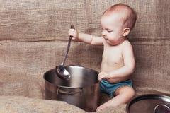 Bébé avec une casserole et une poche image libre de droits