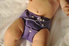 Bébé avec une couche-culotte pourpre bleue de tissu dessus Image stock