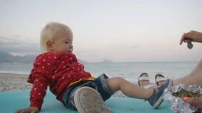Bébé blond ayant l'amusement mangeant une cuillère avec la nourriture d'une main du ` s de mère sur le fond de bord de la mer Enf clips vidéos