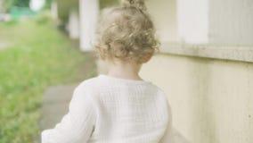 Bébé blond bouclé marchant, tir en gros plan du dos clips vidéos