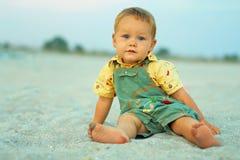 Bébé calme s'asseyant sur la plage de soirée Photos stock