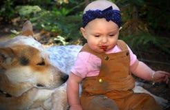 Bébé chauve mangeant la saleté avec le chienchien Images stock