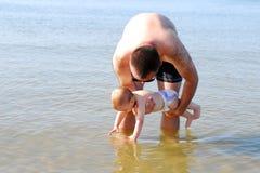 Bébé curieux avec son père touchant la mer Photos stock