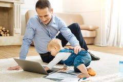 Bébé curieux touchant l'ordinateur portable tout en rampant sur le tapis Images libres de droits