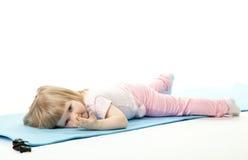 Bébé détendant après sport sur un couvre-tapis de formation image libre de droits