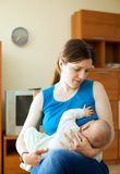 Bébé d'allaitement au sein de mère à la maison Photos libres de droits