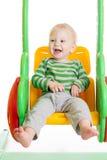 Bébé d'enfant en bas âge jouant sur les oscillations Photos libres de droits