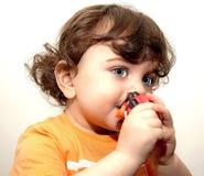 Bébé d'enfant en bas âge tenant cils d'yeux bleus d'un jouet ainsi de longs Photos stock