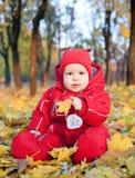 Bébé dans des lames d'automne Photographie stock libre de droits