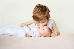 Bébé dans des pyjamas blancs se trouvant sur le sien de retour Des baisers plus anciens de frère Photographie stock