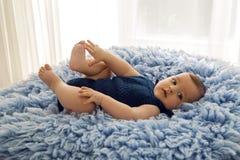 Bébé dans des vêtements d'une salopette tricotés par bleu photos libres de droits