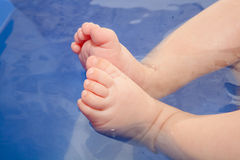 Bébé dans l'eau : Petits pieds Photo stock
