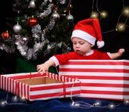 Bébé dans l'intérieur se reposant d'équipement de Santa un boîte-cadeau enveloppé Images libres de droits