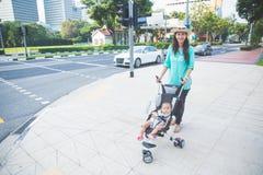 Bébé dans la poussette sur le trottoir de rue Photographie stock