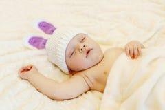 Bébé dans le chapeau tricoté avec le sommeil d'oreilles de lapin se trouvant sur le lit Photographie stock