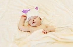 Bébé dans le chapeau tricoté avec un sommeil d'oreilles de lapin se trouvant sur le lit Photo libre de droits