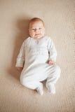 Bébé dans le costume blanc de corps se trouvant sur le sien dos la feuille regardant directement l'appareil-photo Photo libre de droits