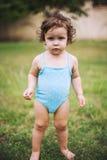 Bébé dans le costume de natation se tenant dans l'herbe Image libre de droits