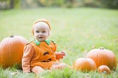 Bébé dans le costume de potiron avec des potirons Photographie stock libre de droits