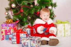Bébé dans le costume de Santa à l'arbre de Noël Photo stock