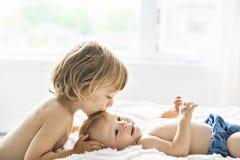 Bébé dans le lit avec son fils de frère donnant un baiser photos stock
