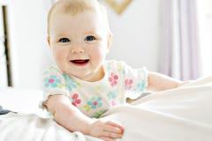 Bébé dans le sembler blanc de literie à la maison gentil image libre de droits