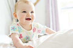 Bébé dans le sembler blanc de literie à la maison gentil photographie stock libre de droits