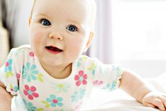 Bébé dans le sembler blanc de literie à la maison gentil photos stock