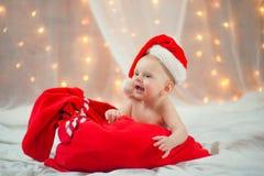 Bébé dans un chapeau de Noël avec le sac de rouge de Santa Claus Image libre de droits