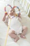 Bébé dans un lit dans le cadre de la forme de coeur Image stock