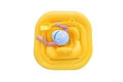 Bébé dans un radeau gonflable jaune d'isolement sur un fond blanc Image stock