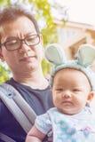 Bébé dans un transporteur de bébé avec le père Image libre de droits