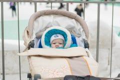 Bébé dans une voiture d'enfant de voiture landau à un jour d'hiver Images stock