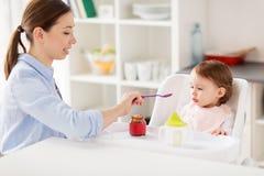 Bébé de alimentation de mère heureuse avec la purée à la maison Photos libres de droits
