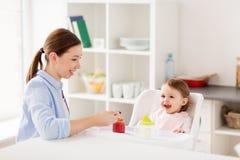 Bébé de alimentation de mère heureuse avec la purée à la maison Photographie stock libre de droits
