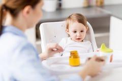 Bébé de alimentation de mère heureuse avec la purée à la maison Image libre de droits