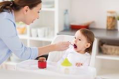 Bébé de alimentation de mère heureuse avec la purée à la maison Photo libre de droits
