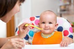 Bébé de alimentation de mère sur la cuisine Images stock