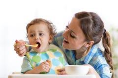 Bébé de alimentation de maman dans le highchair photo libre de droits