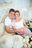 Bébé de attente de famille enceinte heureuse Image stock
