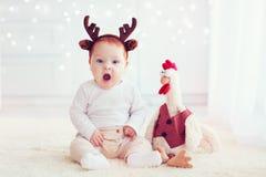 Bébé de baîllement mignon sur le fond de Noël avec le jouet de coq de coq Image libre de droits