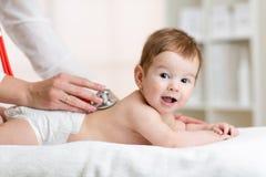 Bébé de examen de docteur avec le stéthoscope Photo stock