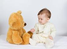 Bébé de petit garçon s'asseyant à côté d'un ours de nounours Photographie stock libre de droits