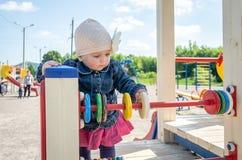 Bébé de petite fille dans le chapeau avec une fleur et une veste bleue de denim et une robe rouge jouant dans le terrain de jeu e Photographie stock