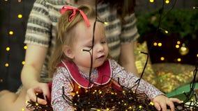 Bébé de petite fille et sa maman s'asseyant sur un fond décoré d'arbre de Noël et jouant avec des guirlandes de Noël banque de vidéos