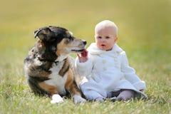Bébé de 1 an précieux s'asseyant dehors avec le chien Photographie stock