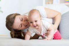 Bébé de rampement drôle avec la mère à la maison images stock